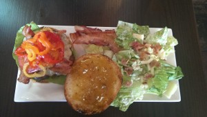 Cajun bacon burger with pineapple jelly, hot peppers, lettuce and a caesar salad.